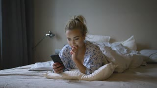 Beautiful young woman with ponytail using smartphone and thinking while lying on soft bed in morning.