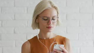 Beautiful young woman with short blond hair and glasses listening to music and browsing smartphone while standing on background of white brick wall