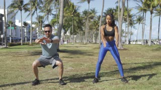 Black woman and man working out together and squatting on green meadow in tropical summer park.