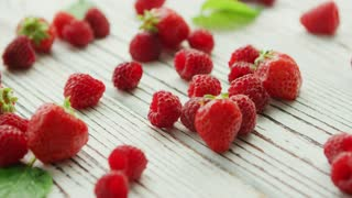Bunch of fresh strawberries and ripe raspberries lying on surface of white timber tabletop near green leaves
