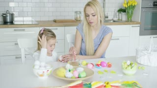 Careful young mother helping little girl to color Easter eggs while sitting at table at light kitchen.