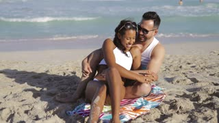 Charming black girl in white bikini embracing with handsome man on towel chilling on beach in sunlight with ocean on background.