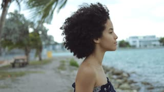 Charming black girl with short curls standing in wind on coastline and looking away with sensuality.