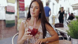 Charming dreaming woman enjoying refreshing drink at table in outside cafe and looking pensively away enjoying time.
