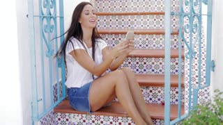 Charming model in casual outfit posing on painted stairs at street of exotic city and watching smartphone smiling happily.