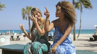 Charming multiracial women in summer clothing having fun while relaxing on ocean beach in sunlight and laughing.