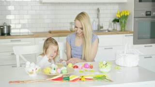 Charming woman and little girl coloring Easter eggs together while sitting by table at light modern kitchen.
