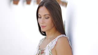 Charming young brunette in light dress leaning on street wall while looking away and daydreaming happily.