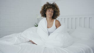 Charming young ethnic model posing on cozy bed wrapped in warm blanket and looking away unwilling to leave for work.