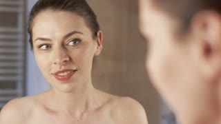 Charming young woman smiling and looking at mirror in bathroom while applying morning cream on skin near eyes.