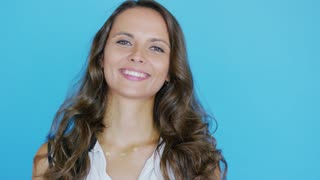 Charming young woman with wavy hair smiling and looking at camera while standing on bright blue background