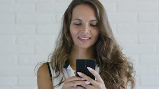 Charming young woman with wavy hair smiling and using modern smartphone while standing on white background