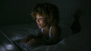 Cheerful ethnic model lying on bed in dark room in light of laptop while using it and communicating.
