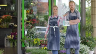 Cheerful man and woman in uniform standing with small tablet 'Open' on background of flower shop and posing at camera with hands crossed.
