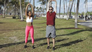 Cheerful man with young black girl in sportswear working out together standing on green meadow in tropical park.