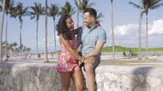 Cheerful stylish black girl with handsome man embracing and looking at each other while sitting on stone fence on seafront.