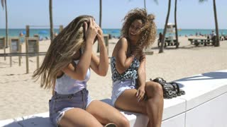 Cheerful young diverse women sitting on fence of seafront and laughing happily while enjoying time in sunlight.