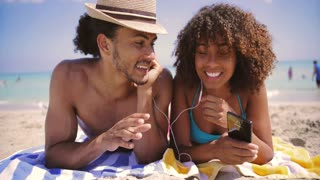 Cheerful young ethnic man and woman lying on sandy beach and listening to music with smartphone at the ocean.