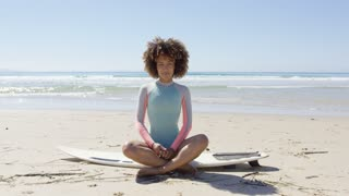 Cheerful young woman on surfboard sitting with hands up and looking at camera in Tarifa beach.