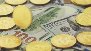 Close-up of shiny golden coins with bitcoin icon falling on top of colorful various dollar bills.