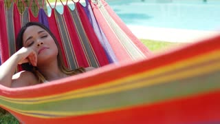 Close up of woman with peaceful expression sleeping in colorful hammock near swimming pool