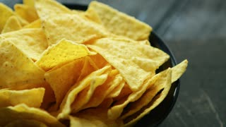 Closeup black plate full of crunchy golden nachos on wooden table
