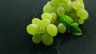 Closeup branch with ripe juicy grape on dark background with water drops