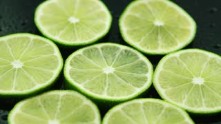 Closeup circle slices of fresh sour green lime on dark background