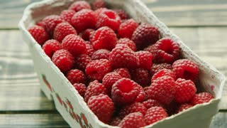 Closeup container full of fresh ripe red raspberry on wooden background