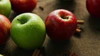 Closeup green and red apple with cinnamon and anise on canvas background