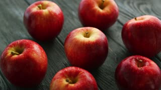 Closeup heap of red fresh apples on dark rough wooden background