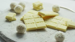 Closeup of arranged white chocolate bars with coconut sweets on wooden board