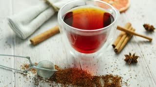 Closeup of glass transparent mug with black tea on table in composition with aromatic spices