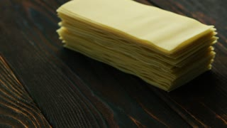 Closeup of stacked uncooked sheets for lasagna cooking composed on wooden table surface