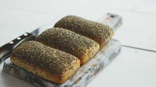 Closeup of whole grain bread with seeds on a rustic wooden board. Side view.