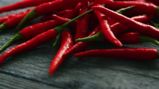 Closeup pile of fresh ripe red hot peppers on dark wooden background