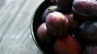 Closeup shot of bowl full of freshly washed wet plums of dark purple colors reflecting soft daylight