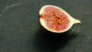 Closeup shot of cut half of delicious fig with red ripe flesh and seeds on rough wood surface