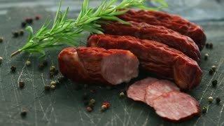 Closeup shot of delectable smoked sausages lying near twig of aromatic rosemary and seeds of hot pepper on scratched cutting board