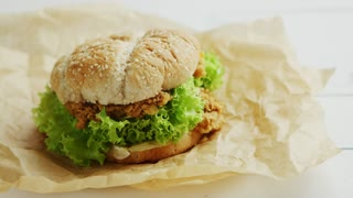 Closeup shot of delicious chicken burger lying on parchment paper on white timber tabletop