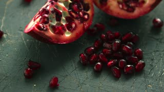 Closeup shot of halves of delicious pomegranate and pile of ruby pomegranate seeds on table