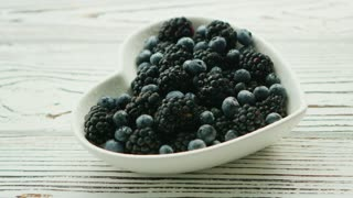 Closeup shot of heart-shaped bowl filled with assortment of blackberries and blueberries on wooden table