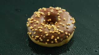 Closeup shot of one round doughnut glazed with chocolate and topped with cereal lying on wet glass surface