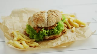 Closeup shot of yummy French fries and tasty chicken burger lying on parchment paper on white timber tabletop