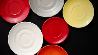 Colorful empty plates and saucers over black background. View from above