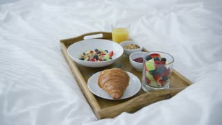 Composed delicious fruit mix in glass and croissant with glass of juice for healthy and filling morning meal served on tray on bed.