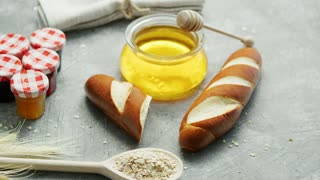 Composition of fresh baguettes with jar of honey on table near spoon of oats and small containers with marmalade