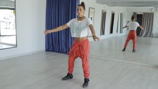 Concentrated young woman in sportive clothing posing and performing contemporary dance in modern studio looking forward.