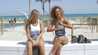 Confident diverse women sitting on tropical coastline in sunshine and talking in leisure relaxing together.