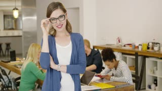 Confident female worker in glasses standing with hands crossed and smiling at camera on background of coworkers at table in office.